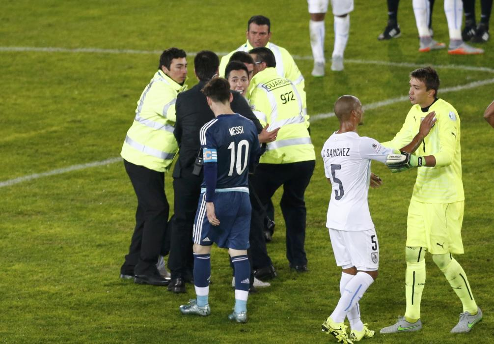 Argentina's Lionel Messi walks by as security personnel detain a fan who ran onto the pitch at the end of the first round Copa America 2015 soccer...