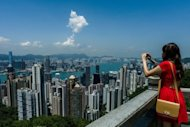 A tourist takes pictures as she visits the peak in Hong Kong in Jul 2012. A plan to allow millions more mainland Chinese to visit Hong Kong was delayed Friday as the southern city said it needed to consult with Beijing over its ability to cope with the influx