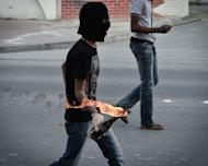 "A Bahraini Shiite Muslim protestor prepares to throw a petrol bomb at security forces during clashes following a demonstration in solidarity with jailed human rights activists in the village of Malikiyah, south of of Manama, on January 7, 2013. The upholding by Bahrain's highest appeals court of lengthy prison terms against 13 opposition activists is ""mind-boggling"", Human Rights Watch said"