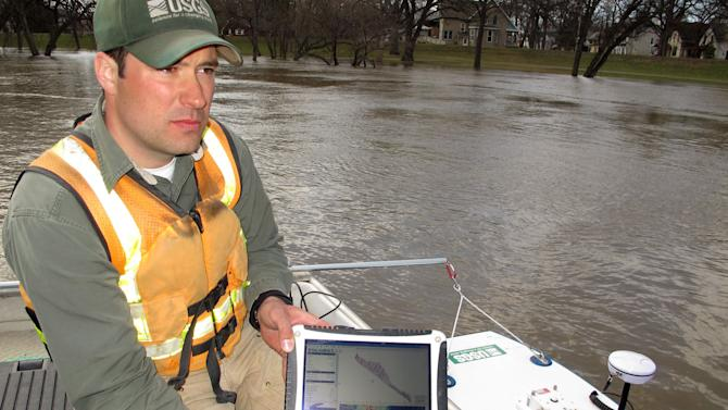 In this April 30, 2013 photo, United States Geological Survey hydrologist Dan Thomas uses a laptop computer to compile results from a sonar device that measures stream flow speed and depth of the Red River in Fargo, N.D. Even with reams of data, forecasting a flood is still an imprecise science. (AP Photo/Dave Kolpack)