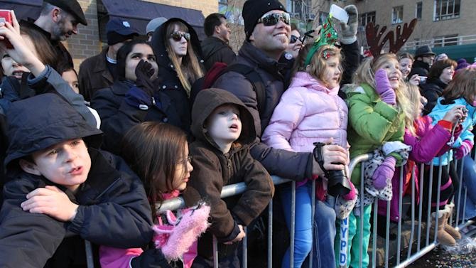 Spectators react as a float with Santa Claus passes by during the 86th Annual Macy's Thanksgiving Day Parade Thursday Nov. 22, 2012, in New York. The annual Macy's Thanksgiving Day Parade put a festive mood in the air in a city still coping with the aftermath of Superstorm Sandy. (AP Photo/Tina Fineberg)
