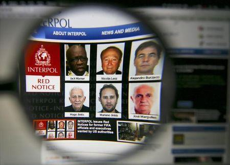 The homepage of the Interpol website is seen through a magnifying glass in this picture illustration taken in Berlin