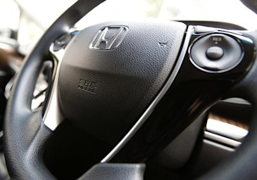The logo of Honda Motor Co and an airbag logo are seen on a steering wheel of a car displayed at the company's showroom in Tokyo June 17, 2014. (REUTE...