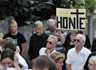 Protesters hold a banner reading 'Shame' during a protest outside a convent in Malonne that has agreed to house on parole Michelle Martin, the ex-wife and accomplice of notorious Belgian paedophile serial killer Marc Dutroux