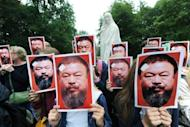 Demonstrators pose with portraits of Chinese artist Ai Weiwei on August 24, at the Karlsaue park in Kassel, Germany. A Beijing court has rejected Ai's appeal against a $2.4 million fine for tax evasion that he calls politically motivated