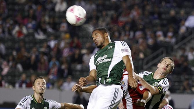 Portland Timbers forward Ryan Johnson (9) heads the corner kick away as Portland Timbers midfielder Will Johnson, right, defends against Chivas USA forward Erick Torres, center, during the second half of an MLS soccer match, Saturday, Oct. 26, 2013, in Carson, Calif. Timbers won the match 5-0