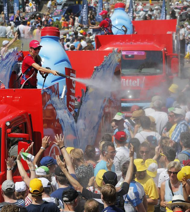 The publicity caravan sprays water on spectators as they wait for the start of the first stage of the Tour de France cycling race, an individual time trial over 13.8 kilometers (8.57 miles), with star