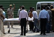 Hospital staff and family members of the man accused in the New Delhi gang-rape case, 34-year-old Ram Singh, move his body into an ambulance car at a hospital in New Delhi, on March 12, 2013. A probe into the death of Singh, suspected of gang-raping a student on a New Delhi bus last December, blames jail officials for failing to monitor him adequately, according to an Indian media report