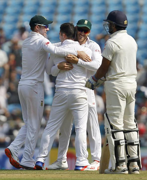 South Africa's Elgar is congratulated by his teammates de Villiers and du Plessis after he took the wicket of India's Dhawan as Vijay watches on the first day of their third test cricket match