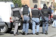 Masked policemen walk past the building where self-professed Al-Qaeda militant Mohamed Merah, was living in Toulouse, southwestern France. French authorities have rejected charges that intelligence failures allowed Merah to kill seven people, insisting there was no evidence he was anything but a lone wolf with no ties to Al-Qaeda