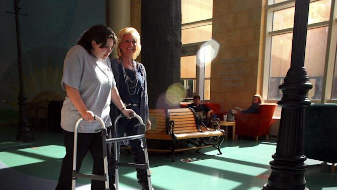 FILE - In this Feb. 20, 2012 file photo, Teagan Marti, of Parkland, Fla., left, and her mother, Julie, walk to the entrance of American Family Childrens' Hospital in Madison, Wis. Actor Charlie Sheen is gifting the $10,000 to pay for a therapy dog to help Teagan who almost died after plummeting 100-feet from a Wisconsin amusement park ride in 2010. (AP Photo/Wisconsin State Journal, Craig Schreiner, File)
