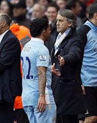 Manchester City manager Roberto Mancini (R) and Carlos Tevez on April 8. Mancini, who had previously said Tevez would never play for the club again, has been forced to reverse his stance during the run-in, particularly after ill-discipline saw Mario Balotelli sidelined for three games