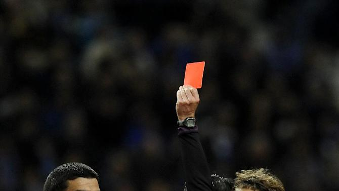 Belenenses'  Joao Afonso, left, is shown a red card by referee Carlos Xistra, with Joao Meira at right, in a Portuguese League soccer match with FC Porto at the Dragao stadium in Porto, Portugal, Sunday, March 23, 2014. Porto won 1-0