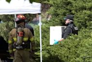 "A police officer carries out evidence in a box from the apartment of the James Holmes in Aurora, Colorado. Police believe they have defused the ""remaining major threats"" in alleged Batman gunman Holmes's booby-trapped apartment, they said Saturday, adding that the devices were designed to kill"