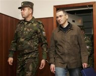 Oil tycoon Mikhail Khodorkovsky (R) is escorted by a security officer before an appeal hearing against his fraud conviction in Moscow City Court in this September 20, 2005 file photo. REUTERS/Sergei Karpukhin/Files