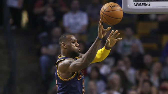 Cleveland Cavaliers forward LeBron James, top, passes as Boston Celtics forward Jae Crowder, left, looks on in the first quarter of a first-round NBA playoff basketball game in Boston, Sunday, April 26, 2015. (AP Photo/Steven Senne)
