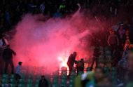 Flares are thrown in the stadium during clashes after a football match between Egypt's Al-Ahly and Al-Masry teams in Port Said, on February 1, 2012. A 13-year-old boy has been shot dead when Egyptian security forces clashed with fans protesting against a ban on Al-Masry football club over the deadly stadium riot