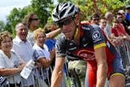 Fans look at Armstrong riding to the signature ceremony prior to the start of the 198 km and 18th stage of the 2010 Tour de France. The US anti-doping agency banned Armstrong for life on Friday, stripping him of the record seven Tour de France titles that helped him become an inspirational icon of US sports