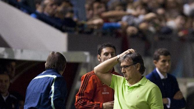 FC Barcelona's coach Gerardo Martino of Argentina, foregtound, gestures while  Osasuna's coach Javier Gracia, right, looks at him during their Spanish League soccer match, at El Sadar stadium, in Pamplona northern Spain on Saturday, Oct. 19, 2013