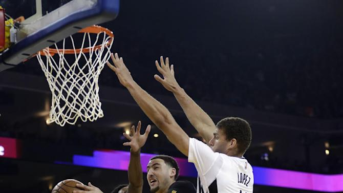 Golden State Warriors' Klay Thompson, center left, drives to the basket as Brooklyn Nets' Brook Lopez, center right, and Randy Foye (2) defend during the first half of an NBA basketball game Saturday, Feb. 25, 2017, in Oakland, Calif. (AP Photo/Marcio Jose Sanchez)