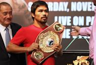 Philippine boxing icon Manny Pacquiao holds the title belt after posing for photographs during a pre-fight press conference in Macau on November 20, 2013