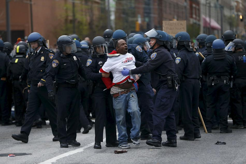 Police detain a protester at a rally to protest the death of Freddie Gray who died following an arrest in Baltimore