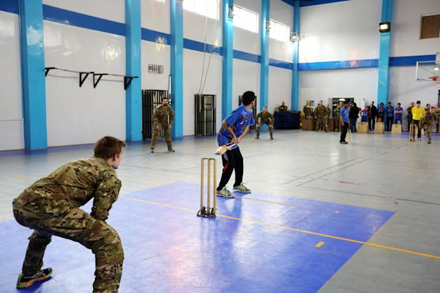 An Afghan player bats during an exhibition cricket match between Afghan local employees with Australian soldiers in NATO headquarters, at Kabul, Afghanistan, Monday, March, 2, 2015. After setting up a