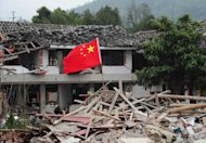 A Chinese national flag flies in the ruins of houses in Longmen, a town close to the epicentre of the earthquake that hit the city in Ya'an, Sichuan province, on April 21, 2013. The life of many in Longmen, and across the wider county of Lushan, changed forever when the devastating earthquake struck on Saturday morning, leaving more than 200 people dead or missing