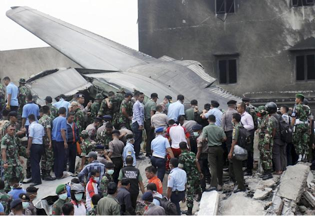 Rescuers search for victims at the site where an air force cargo plane crashed in Medan, North Sumatra, Indonesia, Tuesday, June 30, 2015. The C-130 Hercules plane crashed into a residential neighborh