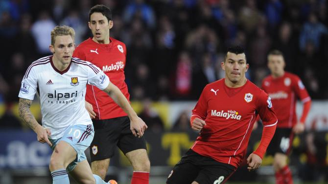Cardiff City's Medel challenges West Ham United's Collison during their English Premier League soccer match in Cardiff