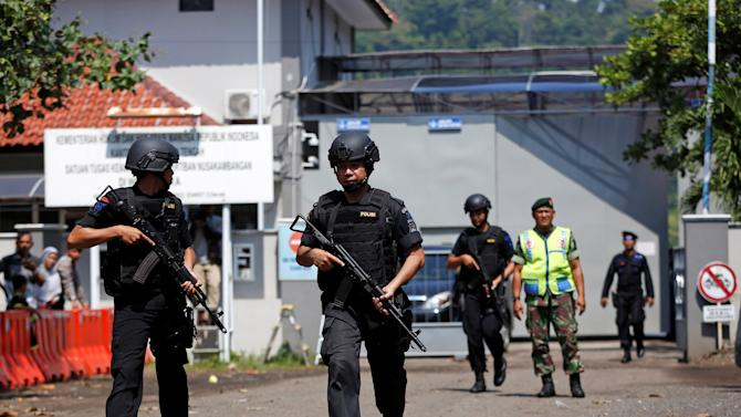 Armed police walk near the gate to the ferry port for the prison island of Nusa Kambangan island, ahead of the expected execution of 14 drug convicts, including at least four foreigners, in Cilacap