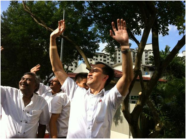 PAP's Dr Koh Poh Koon and company wave as the sun shines down. But few supporters can be seen on the road.