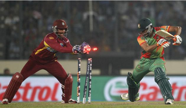 West Indies' Ramdin breaks the wicket to dismiss Haque successfully during their ICC Twenty20 World Cup match in Dhaka
