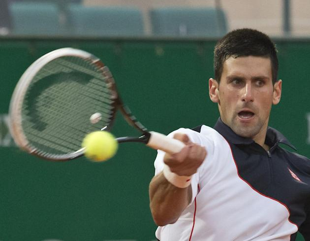 Novak Djokovic of Serbia, returns the ball to Guillermo Garcia-Lopez of Spain during their quarterfinals match of the Monte Carlo Tennis Masters tournament in Monaco, Friday, April 18, 2014