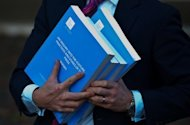 "A journalist holds a copy of the Leveson report in London on November 29, 2012. Leveson concluded in his final report that British newspapers had ""wreaked havoc with the lives of innocent people"" and recommended a complete overhaul of their system of self-regulation, backed by a new law."