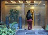 "An Indian surrogate mother enters the Surrogacy Centre India (SCI) clinic in New Delhi on February 5, 2013. While the Indian government has been pushing the country as a medical tourism destination, the issue of wealthy foreigners paying poor Indians to have babies has raised ethical concerns in many Indian minds about ""baby factories"""