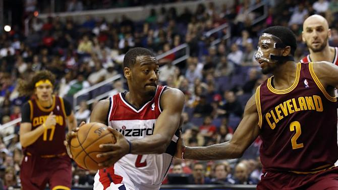 Washington Wizards guard John Wall (2) drives with the ball as he guarded by Cleveland Cavaliers guard Kyrie Irving (2) in overtime of an NBA basketball game on Saturday, Nov. 16, 2013, in Washington. The Cavaliers won 103-96 in overtime