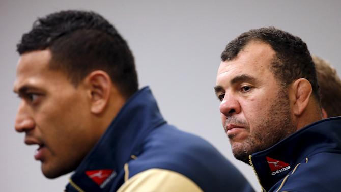 Australian Wallabies rugby union team coach Michael Cheika listens to player Israel Folau speak during a media conference at the Sydney Cricket Ground, Australia