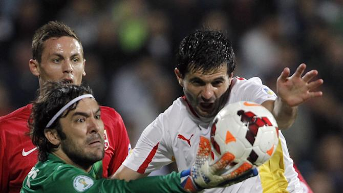 Serbia's goalkeeper Vladimir Stojkovic, left , challenges for the ball with Macedonia's Boban Grncarov during their World Cup 2014 Group A qualifying soccer match at the City Stadium in Jagodina, Serbia, Tuesday, Oct. 15, 2013