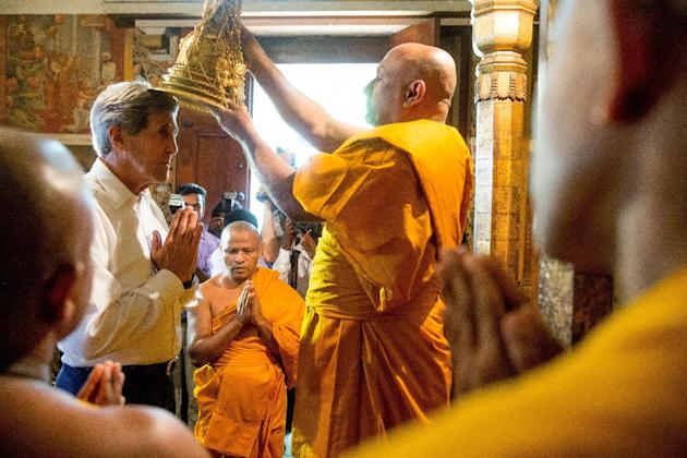 Head monk Venerable Professor Kollupitiya Mahinda Sangharakkhita Mahathera, center  performs a health and happiness blessing on U.S. Secretary of State John Kerry inside the ancient Kelaniya Temple, S