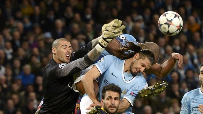 Barcelona's goalkeeper Valdes punches the ball past Barcelona's Fabregas and Manchester City's Kompany and Demichelis during their Champions League round of 16 first leg soccer match against Barcelona at the Etihad Stadium in Manchester