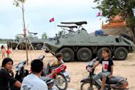 Cambodian children sit on motorbikes near armored personnel carriers on the outskirts of Phnom Penh on August 8, 2013. Cambodia has deployed armed forces in the capital Phnom Penh in case of mass demonstrations following the country's disputed election