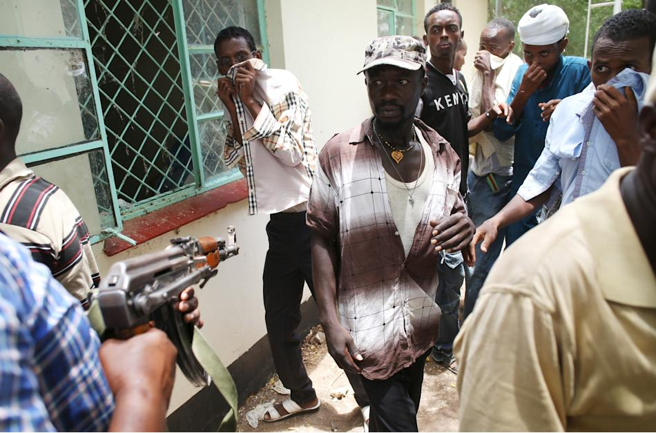 A policeman points his gun as he tries to push back people who came to see the bodies of suspected Garissa University College attackers in a morgue in Garissa