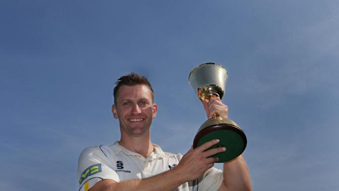 Warwickshire captain Jim Troughton holds the LV County Championship trophy aloft after victory over Worcestershire