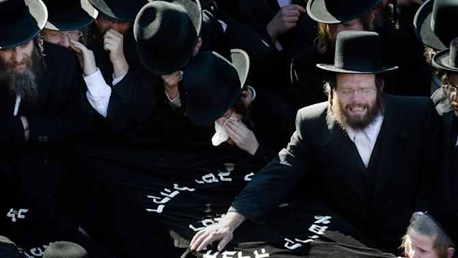 Members of the Satmar Orthodox Jewish community grieve over the coffins at the funeral for two expectant parents who were killed in a car accident, Sunday, March 3, 2013, in the Brooklyn borough of New York. A driver struck the car early Sunday morning, killing both parents while their baby, who was born prematurely, survived and is in critical condition. (AP Photo/John Minchillo)