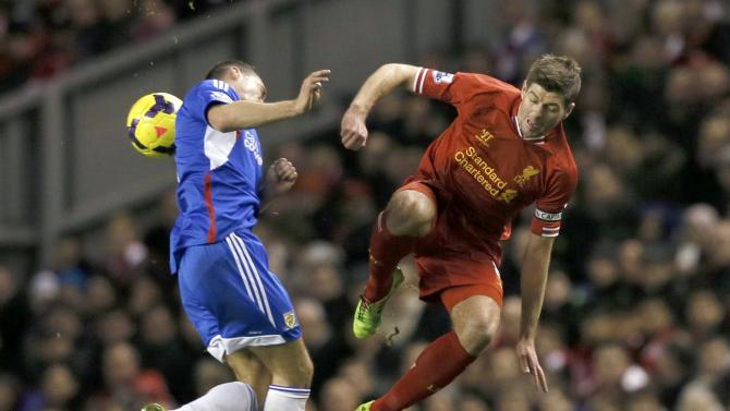 Liverpool's Gerrard challenges Hull City's Chester in Liverpool
