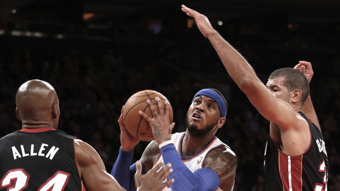 New York Knicks' Carmelo Anthony (7) drives between Miami Heat's Ray Allen (34) and Shane Battier during the first half of an NBA basketball game Saturday, Feb. 1, 2014, in New York. (AP Photo/Jason DeCrow)