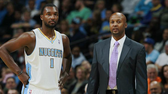 Denver Nuggets head coach Brian Shaw, right, confers with forward Jordan Hamilton during a break in play against the San Antonio Spurs in the first quarter of an NBA preseason basketball game in Denver on Monday, Oct. 14, 2013. Shaw is making his debut as the Nuggets heads coach