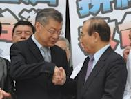 Taiwanese Premier Sean Chen (L) shakes hands with Parliamentary speaker Wang Jin-pyng after a no-confidence vote in Taipei on September 22. Chen comfortably survived a no-confidence vote brought by opposition parties Saturday over what they see as his cabinet's failure to curb rising unemployment and inflation