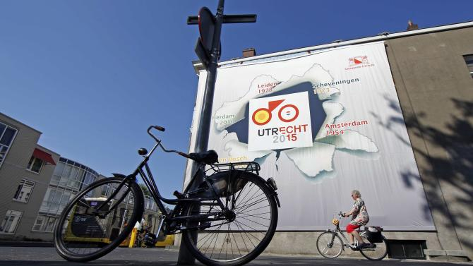 """A cyclist rides past a giant poster announcing """"The Grand Depart"""" of the Tour de France cycling race in Utrecht"""